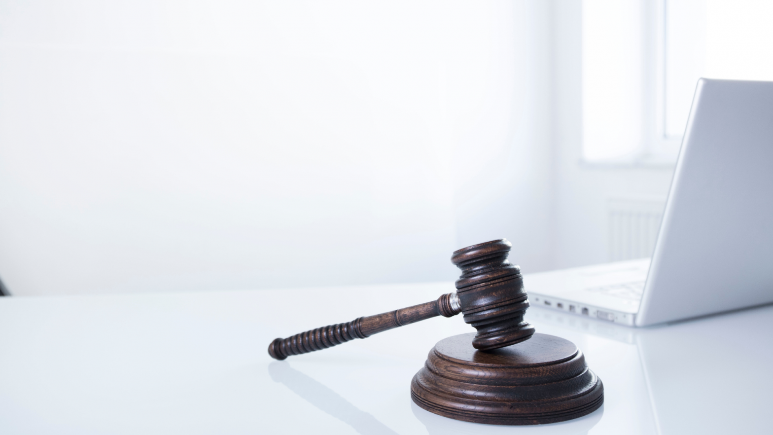 Judge's gavel next to a laptop